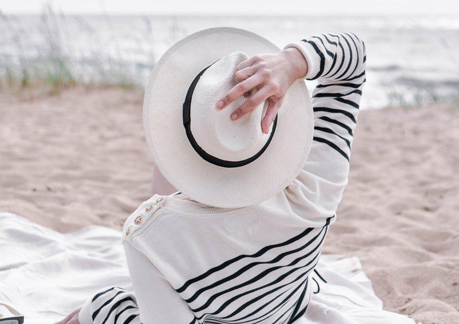 Garota na praia segurando chapéu curtindo vida independente